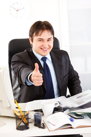 Pleased business man sitting at office desk and showing  thumbs up gesture  photo