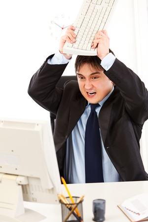 Angry  businessman sitting at office desk and destroying computer using keyboard  Stock Photo - 8841793