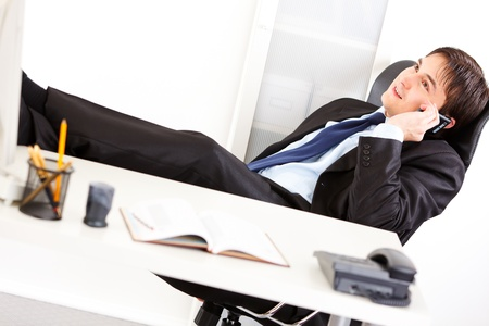 Happy  businessman sitting  with feet on desk and talking on mobile phone in the office  photo