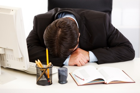 Tired business man sleeping at  desk in  office   photo
