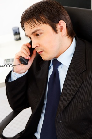 Attentive  young business man talking on  telephone in office
