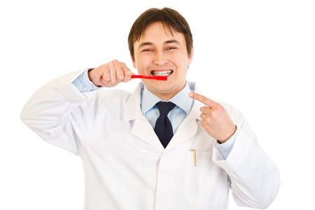 Smiling dentist pointing finger on toothbrush   photo