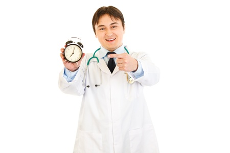 Smiling  medical doctor pointing finger on  alarm clock  photo