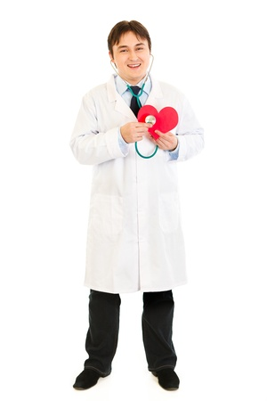 Smiling doctor holding stethoscope on heart shape paper     photo
