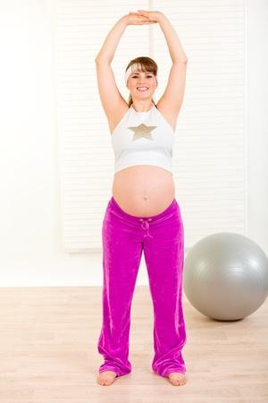 haciendo ejercicio: Sonriente y bella mujer embarazada haciendo ejercicio en la sala de estar  Foto de archivo