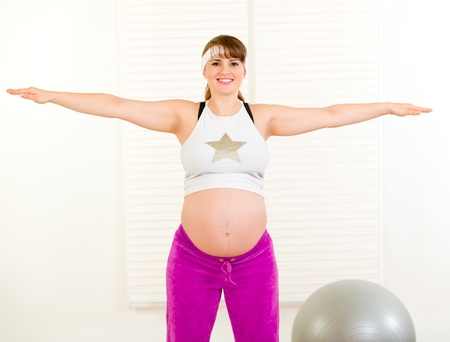 Smiling beautiful pregnant woman doing exercise in living room  photo