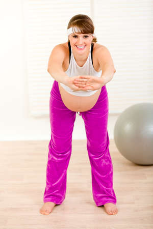 Smiling beautiful pregnant woman doing gymnastics  at living room  photo