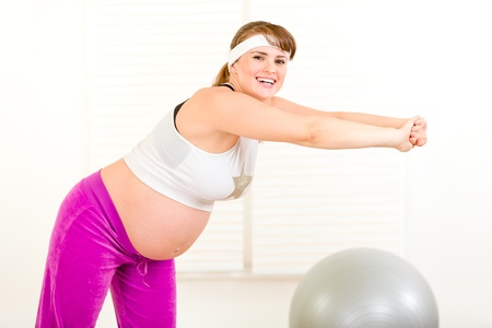 Smiling beautiful pregnant woman doing gymnastics in living room  photo