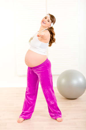 Smiling beautiful pregnant female doing exercise at living room  photo