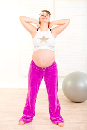 Smiling beautiful pregnant woman doing exercise at living room  photo