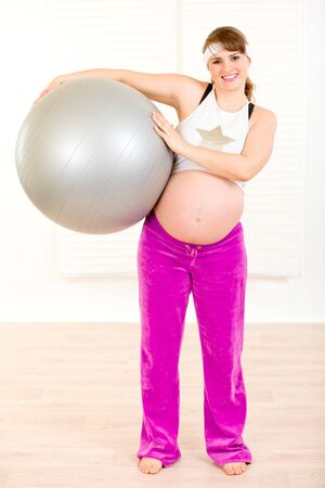 Smiling beautiful pregnant woman at home holding fitness ball in hands   photo