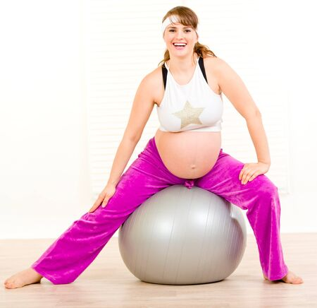 Smiling beautiful pregnant woman doing exercises on  fitness ball at living room Stock Photo - 8842703