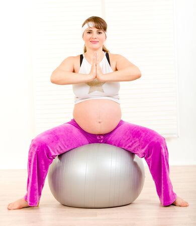 Smiling beautiful pregnant woman doing pilates exercises on gray ball 