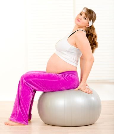 Smiling beautiful pregnant woman doing pilates exercises on gray ball   photo