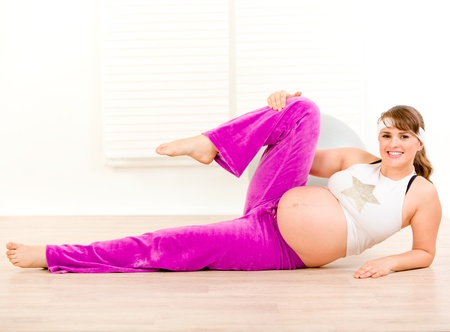 Smiling beautiful pregnant woman doing aerobics exercise at home  photo