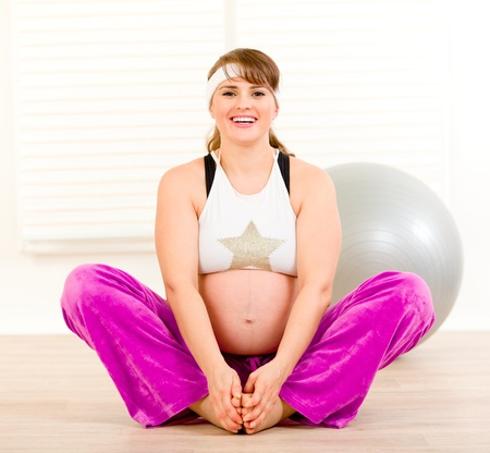 Smiling beautiful pregnant woman doing stretching exercises   photo