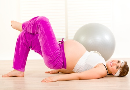 Smiling beautiful pregnant woman doing exercise at living room Stock Photo - 8843331