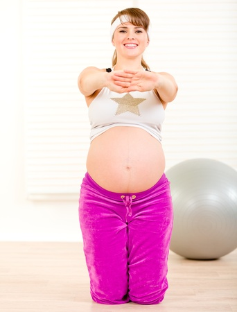 Smiling beautiful pregnant woman doing fitness exercises at home  photo