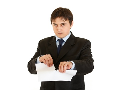 Displeased modern businessman tearing document  photo