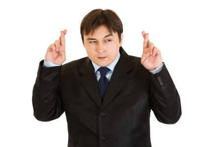 crossed fingers: Superstitious young businessman holding crossed fingers