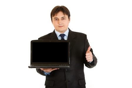 Smiling businessman holding blank screen laptops and showing  thumbs up gesture   photo