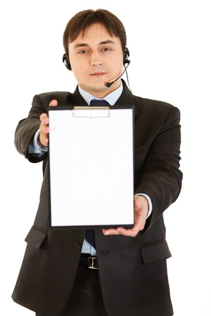 Smiling young businessman with headset holding blank clipboard   photo