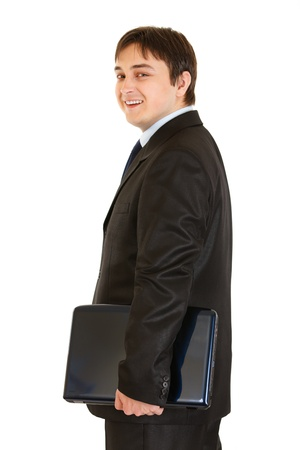 Smiling modern businessman holding laptop   photo