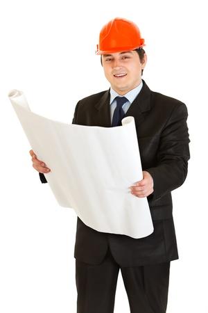 Smiling businessman wearing helmet holding building plan in hand   photo