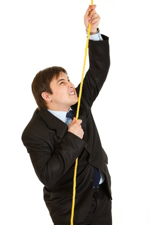 Stubborn businessman climbing up on a rope   photo