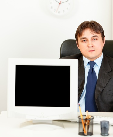 Modern businessman sitting at office desk and showing blank screen monitor  photo