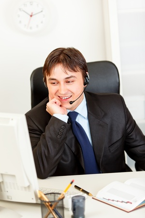 Smiling  business man with  headset sitting at office desk and looking at computer monitor Stock Photo - 8846179
