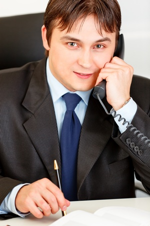 Smiling businessman sitting at office desk and talking on the phone  Stock Photo - 8846368