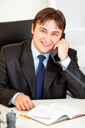 Smiling businessman sitting at office desk and talking on phone Stock Photo - 8846276