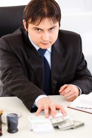 Concentrated business man  sitting at office desk and giving money packs  photo