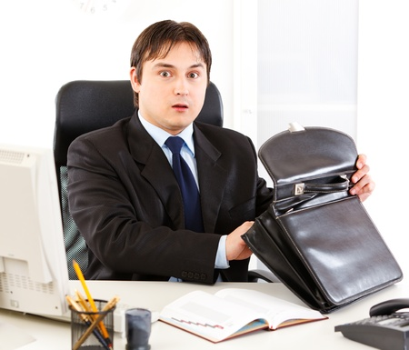 Shocked businessman sitting at office desk and holding open suitcase  photo