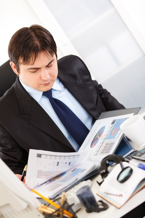 Serious business man sitting at office desk and working  with financial documents Stock Photo - 8846161