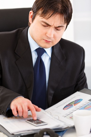 Serious modern business man sitting at office desk and working  with financial documents Stock Photo - 8846255