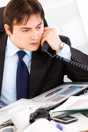 Concentrated modern businessman sitting at office desk and talking on phone  photo