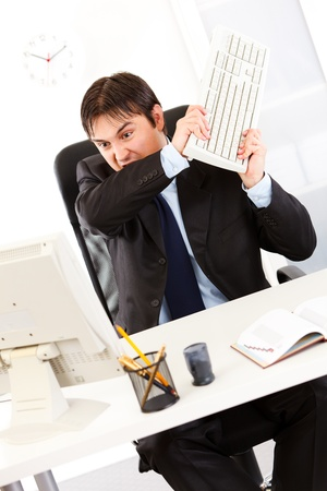 Angry  businessman sitting at office desk and destroying computer using keyboard