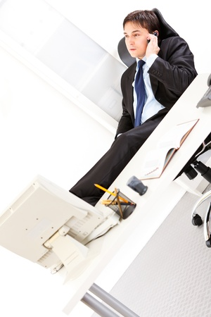 Young  businessman sitting and talking on mobile phone in the office   Stock Photo - 8845964