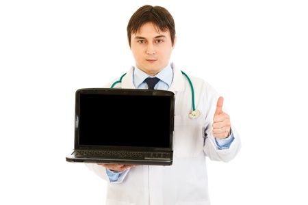 certitude: Medical doctor holding blank screen laptop and showing  thumbs up gesture