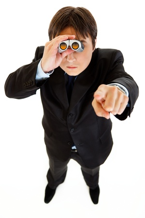 Serious businessman looking through binoculars and pointing finger at someone  photo
