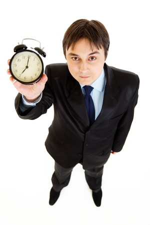 Smiling young businessman holding alarm clock in hand   photo