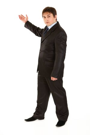 Serious young businessman pointing at a corner  photo