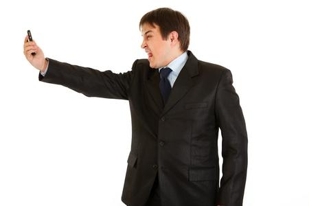 Amazed modern businessman yelling on mobile phone  photo