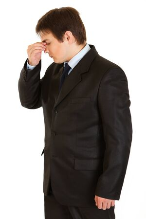 Stressed young  businessman, fingers on his nose  photo