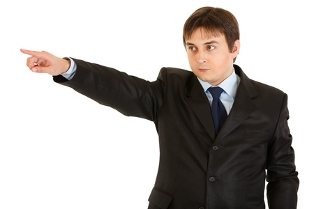Serious young businessman pointing finger in corner isolated on white  photo