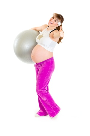 Happy pregnant woman holding fitness ball and showing thumbs up gesture  photo