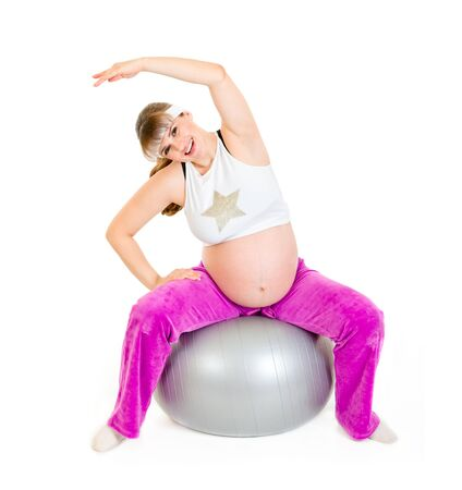 Smiling beautiful pregnant woman doing exercise on  fitness ball   photo