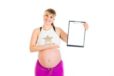 Smiling beautiful pregnant woman pointing on blank clipboard  photo